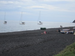 black beach with sailboats